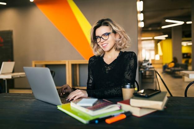 Mujer joven que trabaja en la computadora portátil en la oficina de trabajo conjunto