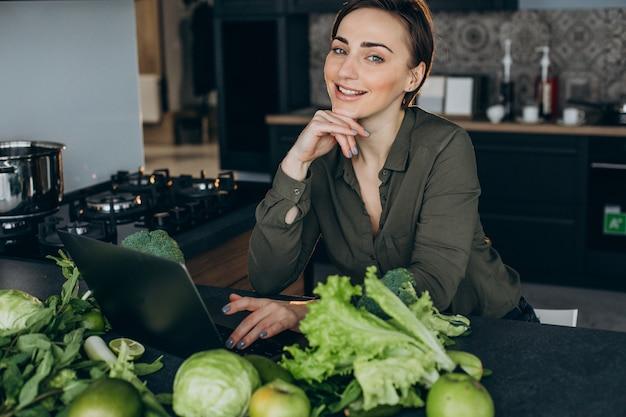 Mujer joven que trabaja en la computadora portátil y sentado en la cocina