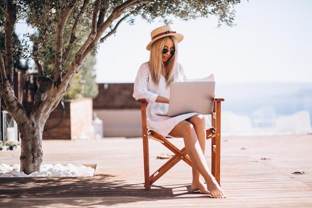 Mujer joven que trabaja en la computadora portátil en vacaciones
