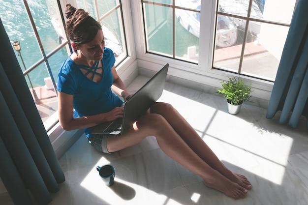 Mujer joven que trabaja con la computadora portátil en la ventana de su casa sobre el puerto deportivo
