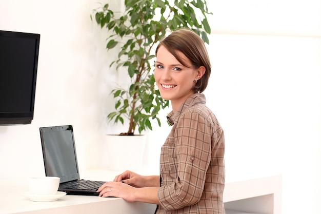 Mujer joven que trabaja con la computadora portátil