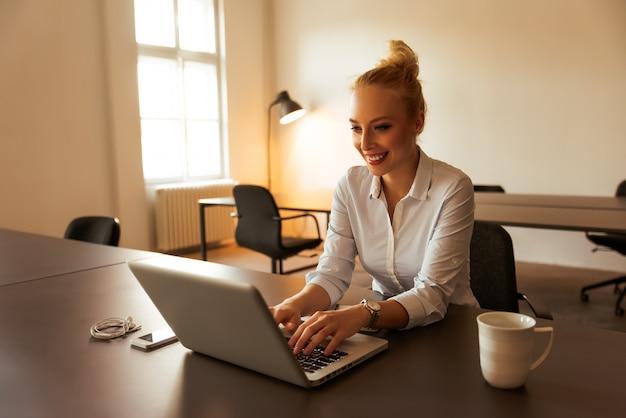 Mujer joven que trabaja en el escritorio de oficina moderno con una computadora portátil