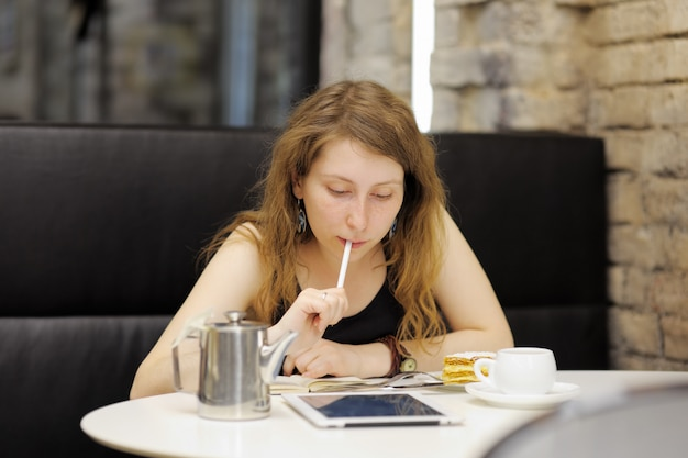 Mujer joven que trabaja o estudia en su tableta en un café