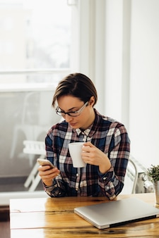 Mujer joven que trabaja en la oficina doméstica cecking móvil con una taza de té