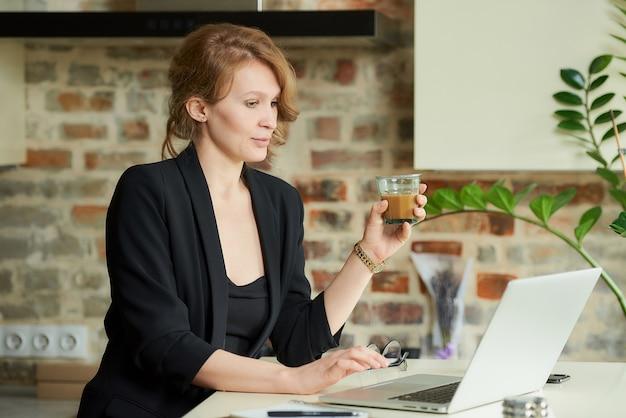 Una mujer joven que trabaja remotamente en su cocina. una jefa con un café escuchando una discusión de un proyecto con empleados en una videoconferencia en casa.
