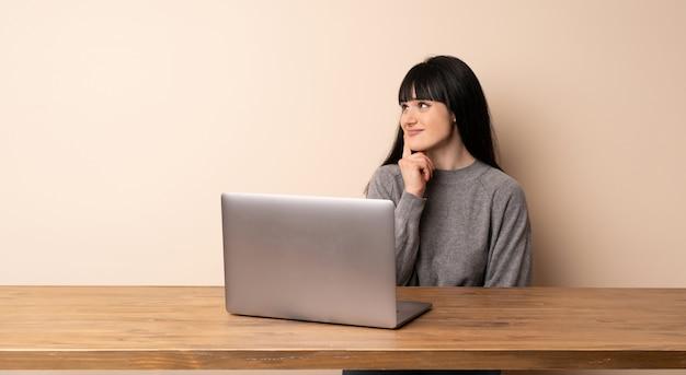 Mujer joven que trabaja con su computadora portátil pensando en una idea mientras mira hacia arriba