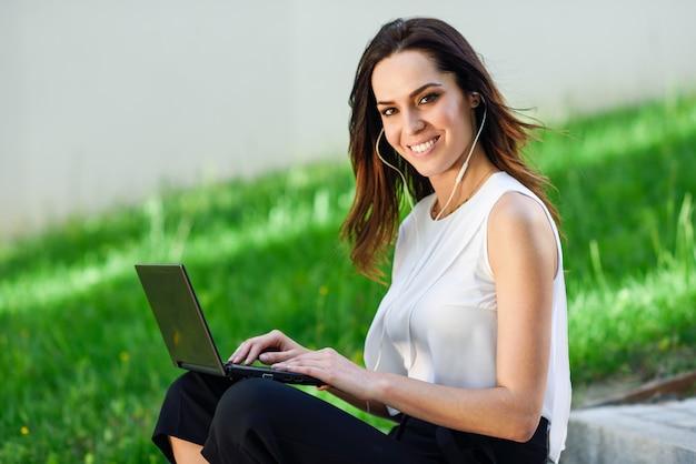 Mujer joven que trabaja con su computadora portátil que se sienta en el piso.