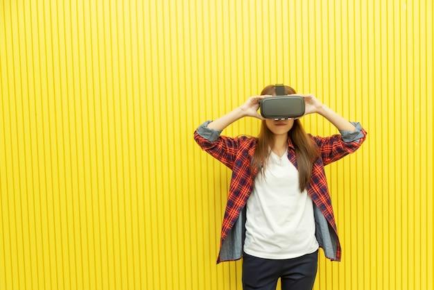 Mujer joven que usa la cabeza de realidad virtual para ver las películas en 3d. tecnología moderna para el entretenimiento del hogar.