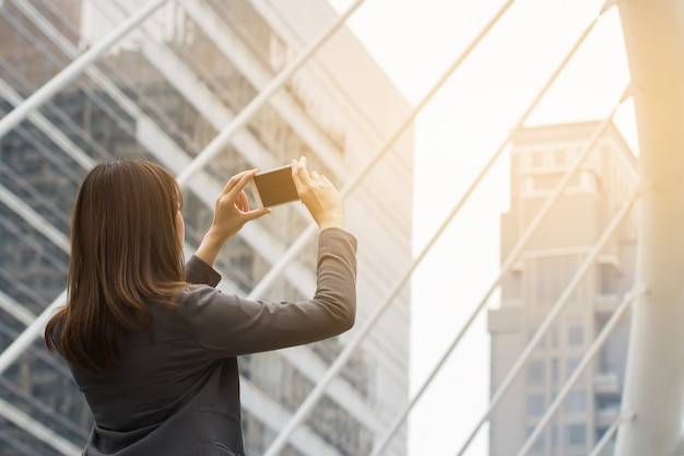 Mujer joven que usa la cámara en el teléfono inteligente para disparar la foto en fondo urbano