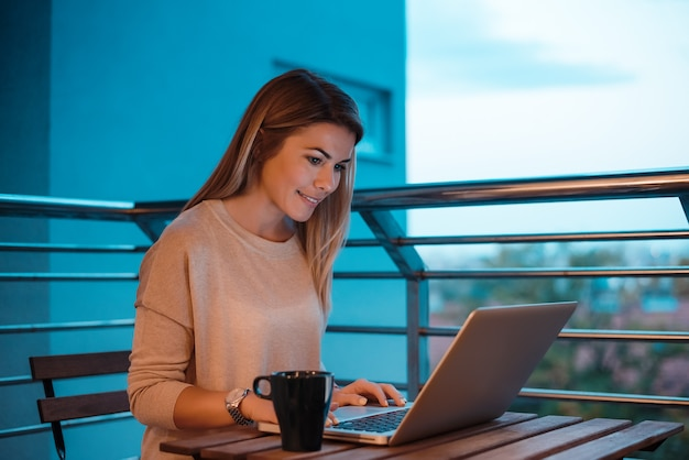 Mujer joven que usa la computadora portátil en el balcón casero.