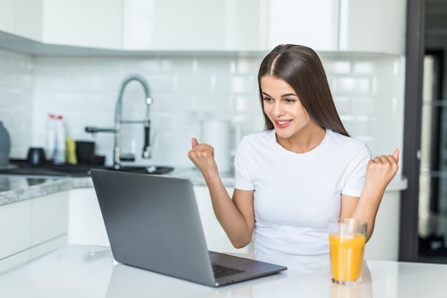 Mujer joven que usa la computadora portátil en la cocina gritando orgullosa y celebrando la victoria y el éxito muy emocionados
