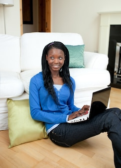 Mujer joven que usa una computadora portátil que se sienta en el piso