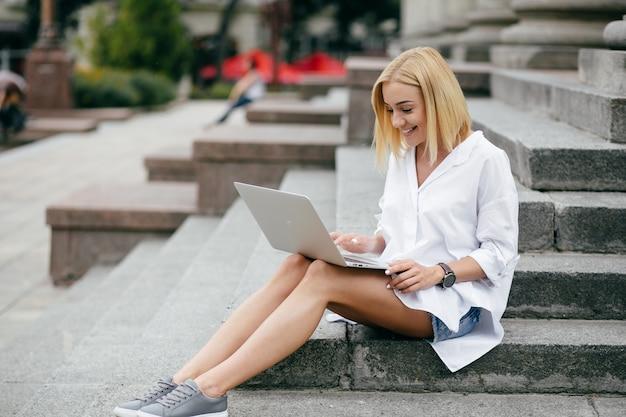 Mujer joven que usa la computadora portátil y el teléfono elegante. muchacha hermosa del estudiante que trabaja en la computadora portátil al aire libre