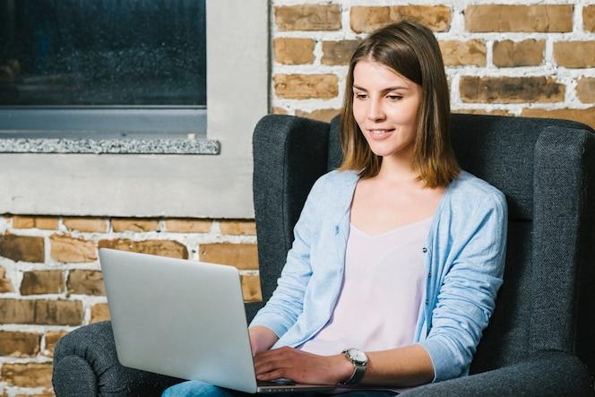 Mujer joven que usa la computadora portátil en el sillón