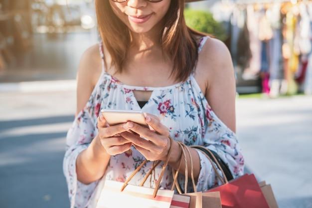 Mujer joven que usa smartphone con los panieres en la alameda de compras en viernes negro, concepto de la forma de vida de la mujer