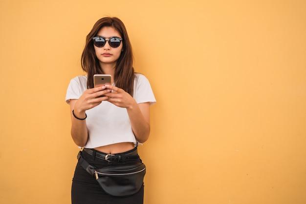 Mujer joven que usa su teléfono móvil