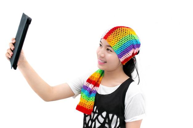 Mujer joven que usa una tableta para el selfie aislado en blanco.