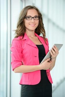 Mujer joven que usa una tableta en su oficina.