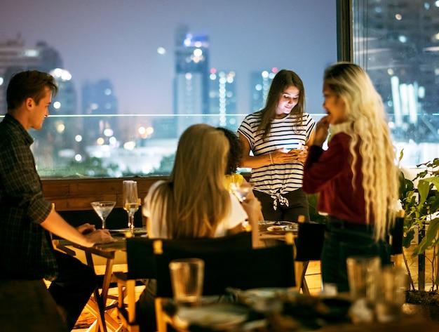 Mujer joven que usa un teléfono inteligente en una cena de noche sin interacción