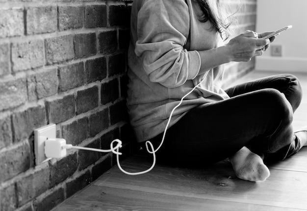 Mujer joven que usa un teléfono inteligente como se está cargando