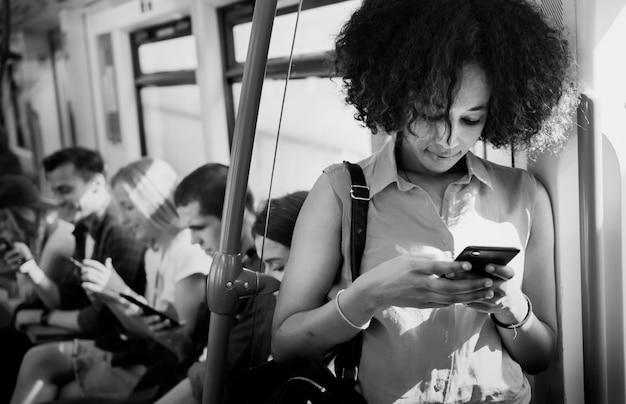 Mujer joven que usa un teléfono inteligente en un metro