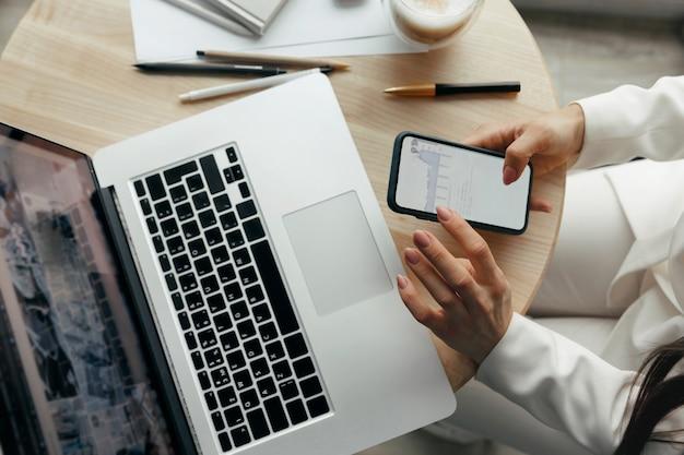 Mujer joven que usa el teléfono y que trabaja en las manos del ordenador portátil de cerca. pago. concepto de compras en línea concepto de blogs. trabajando en casa. concepto de cuarentena y distanciamiento social.