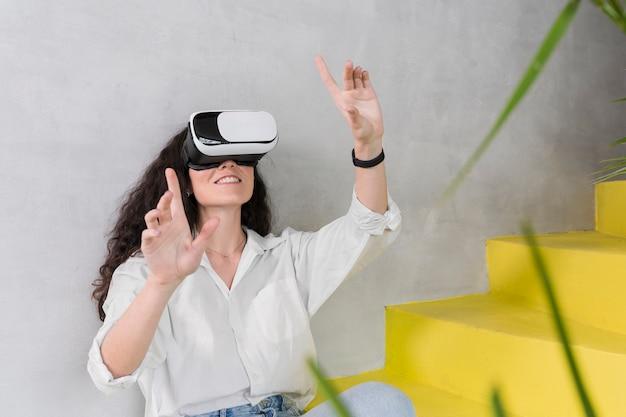 Mujer joven que usa un tiro medio del casco de realidad virtual