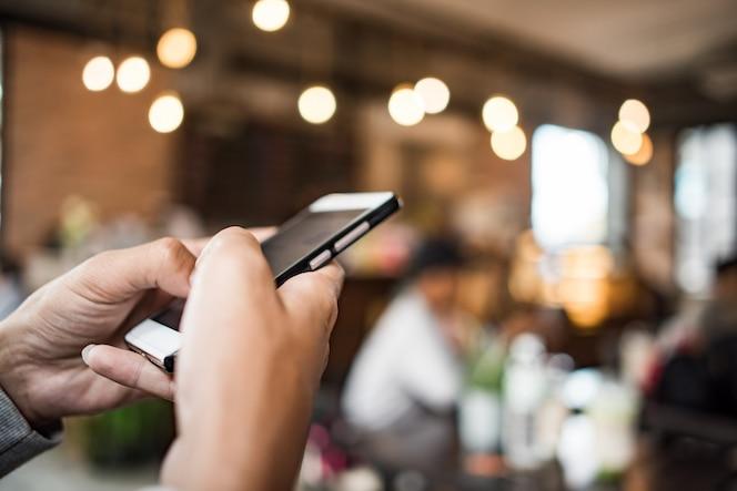 Mujer joven que usa y que mira el smartphone con la sensación feliz