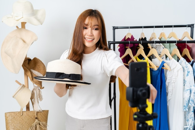 Mujer joven que vende sombrero y ropa en línea por transmisión en vivo de teléfono inteligente, comercio electrónico en línea de negocios en casa