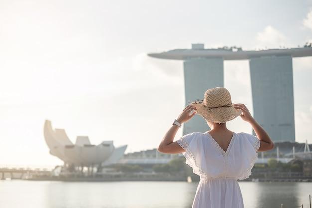 Mujer joven que viaja con el sombrero por la mañana, visita asiática feliz del viajero en el centro de la ciudad de singapur. punto de referencia y popular para las atracciones turísticas. concepto de viaje de asia