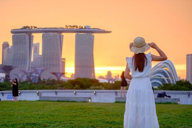 Mujer joven que viaja con el sombrero en la puesta del sol, visita asiática feliz del viajero en el centro de la ciudad de singapur. punto de referencia y popular para las atracciones turísticas. concepto de viaje de asia