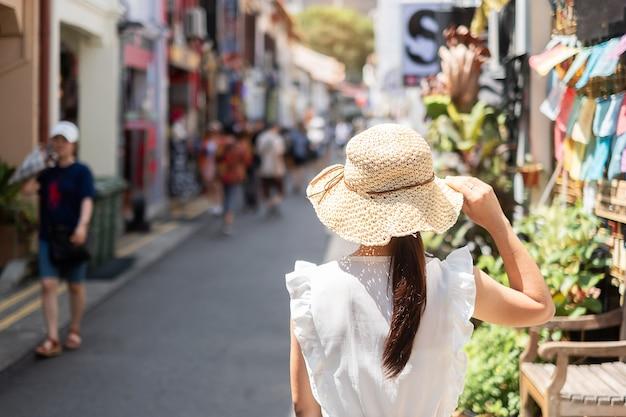 Mujer joven que viaja con vestido blanco y sombrero