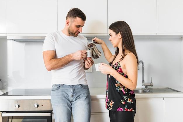 Mujer joven que vierte el café en la taza de su novio