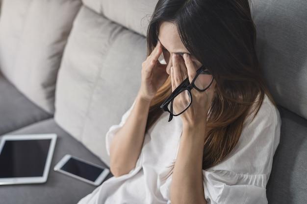 La mujer joven se quita sus vidrios y siiting en el sofá
