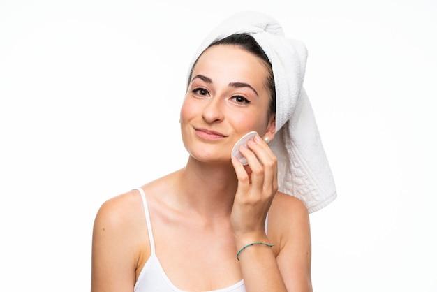 Mujer joven quitando maquillaje de su cara con algodón