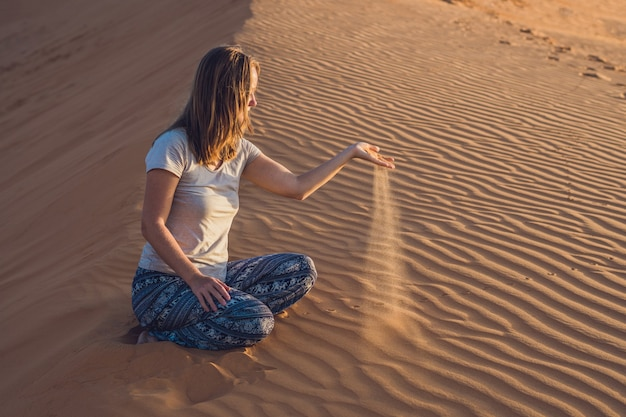 Mujer joven en rad sandy desert al atardecer o al amanecer
