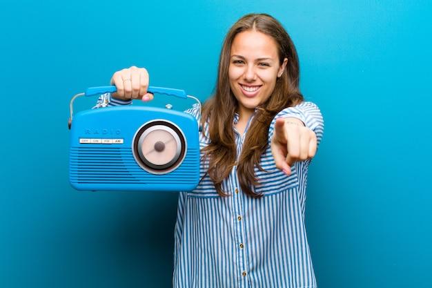 Mujer joven con una radio vintage azul
