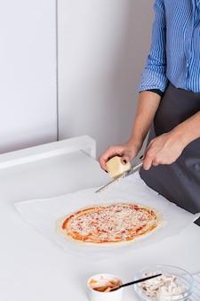 Mujer joven rallar el queso en pizza de masa casera