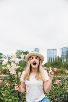 Mujer joven con ramo de flores apuntando el dedo hacia arriba