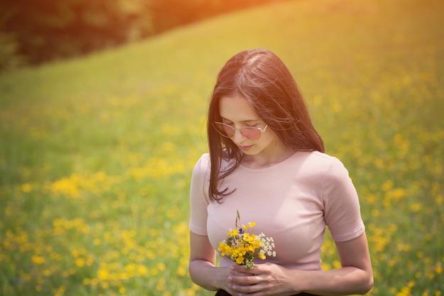 Mujer joven con ramo de flores silvestres un césped soleado. día de verano