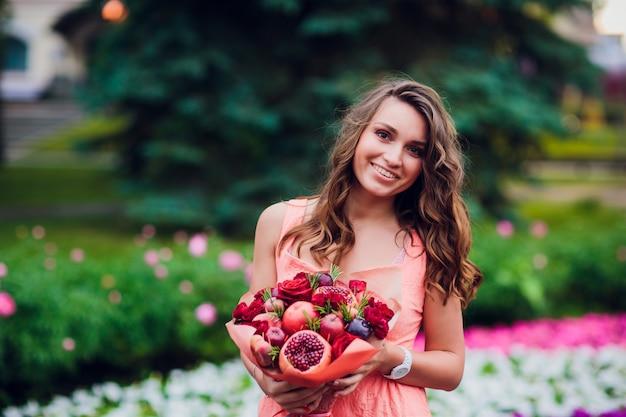 Mujer joven con un ramo de frutas y bayas