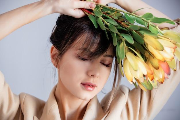 Mujer joven con ramo de leucadendron.