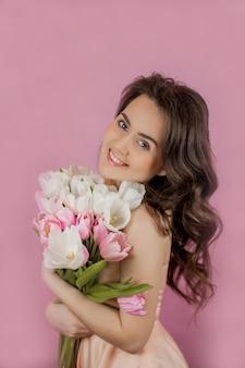 Mujer joven, ramo, de, tulipanes, sonriente, niña, retrato, primavera, rosa, pared