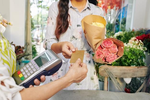 Mujer joven con ramos de flores dando tarjeta de crédito a floristería con terminal de pago en tienda