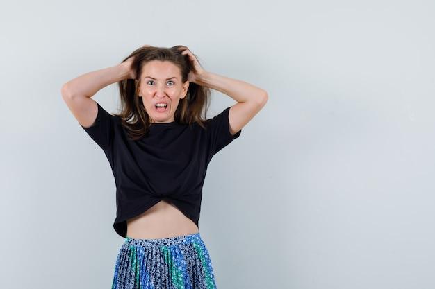 Mujer joven rascándose la cabeza, haciendo muecas en camiseta negra y falda azul y mirando acosado