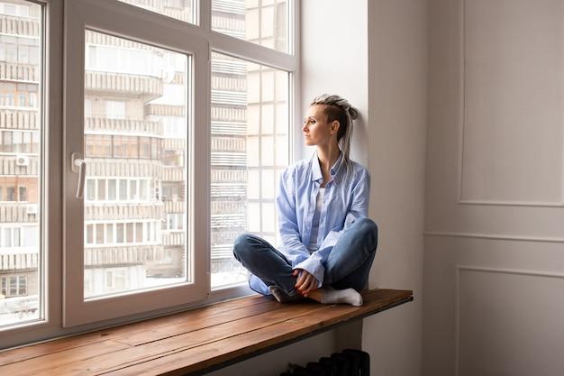Mujer joven con rastas mirando por la ventana