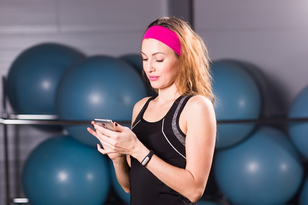 Mujer joven con rastreador de actividad y teléfono inteligente en el gimnasio