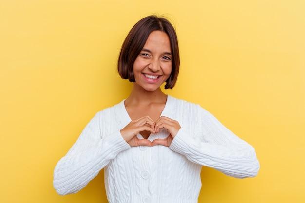 Mujer joven de raza mixta aislada en la pared amarilla sonriendo y mostrando una forma de corazón con las manos.