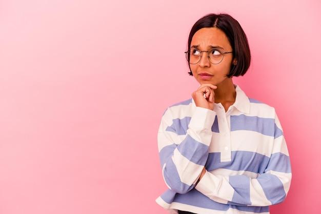 Mujer joven de raza mixta aislada en rosa mirando hacia los lados con expresión dudosa y escéptica.