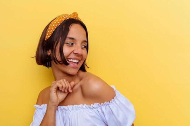 Mujer joven de raza mixta aislada sobre fondo amarillo bailando y divirtiéndose.
